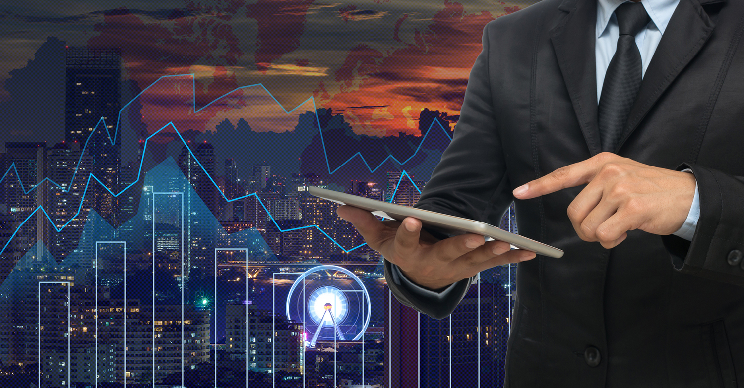 businessman using the tablet on Trading graph on the cityscape a
